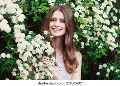 a young girl is standing near the green bush with white blossom