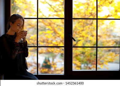 young girl standing near huge window with forest background and drink coffee, tea. autumn sadness concept.  vacation in mountains in autumn. loneliness concept.copy space. stay at home
