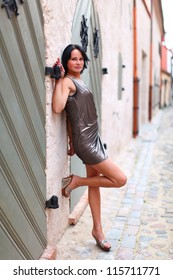 Young girl is standing near to old wooden door in sexual pose at full length on street of Old Riga, Latvia