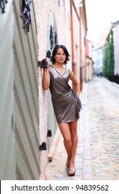 Young girl is standing near to old wooden door at full length on street of Old Riga, Latvia