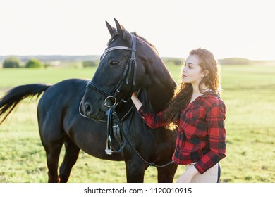Young girl standing next to a beautiful dark horse. Friendship. Horseriding.