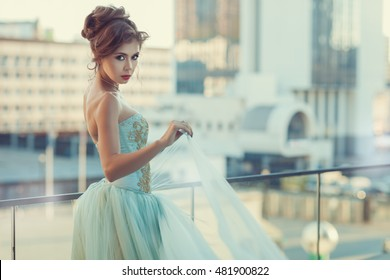 Young girl standing on the balcony, her dress with a corset gently blue color.