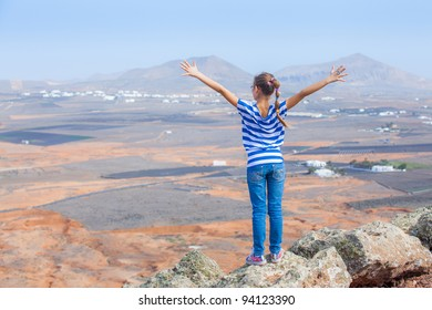 Young girl standing on cliff's edge and looking to a sky with raised hands