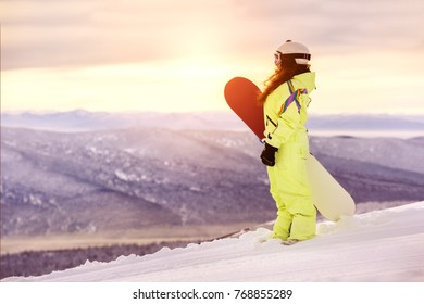 Young girl is standing with snowboard at ski clope and looking at sunrise