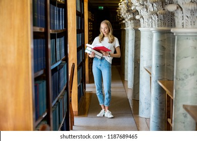 Young girl standing in traditional old library at bookshelves, holding stack of books.. Smiling student searching, studying. Higher education.