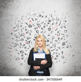 a young girl standing at a wall holding note books, white wall with small pictures at the background, a concept of choice and studying