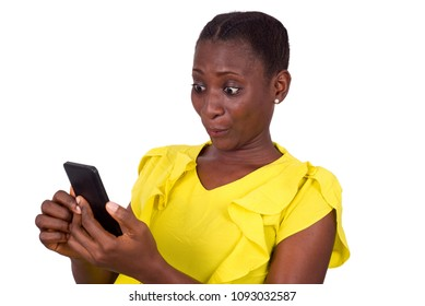 young girl standing in yellow camisole with surprise looks at her mobile phone.