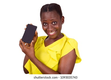 young girl standing in yellow camisole shows her mobile phone while smiling at the camera.