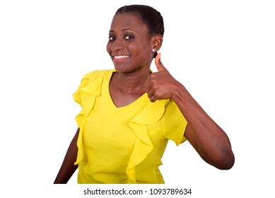 young girl standing in yellow camisole making thumb sign smiling on camera.