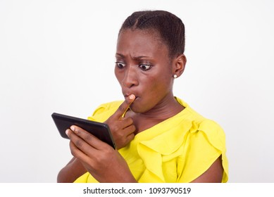 young girl standing in yellow camisole looks at her mobile phone, surprised.