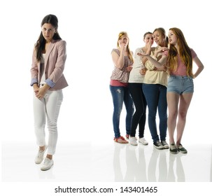A young girl stands alone on the left edge of the screen, her four girlfriends are in the background and gossip about them.