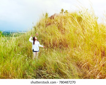 The young girl stands in the meadow on the mountain at winter.
