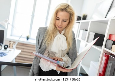 A young girl stands near a rack in the office and scrolls through a folder with documents.