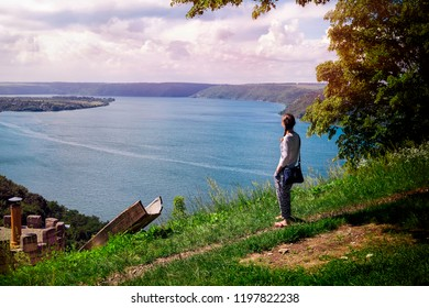 Young girl stands on a hill and looks into the distance. Below is the Dniester River