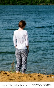 Young girl stands on the river bank and looks at the water. Standing back