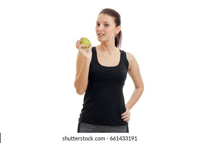 a young girl stands in the Studio looks into the camera and eats Apple