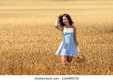 A young girl stands in a wheat field