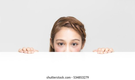 young girl staring something on the white table