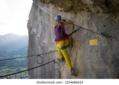 """Young girl starting the via ferrata route called """"Hohenweg"""" by stepping over a safety wire, above Bad Goisern, in Upper Austria, while being attached with safety equipment for via ferrata tours."""