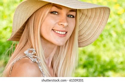 Young girl in straw hat, against summer garden.