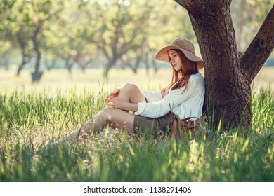young girl in a straw hat travels green meadows. Beautiful red-haired hipster woman in a green garden