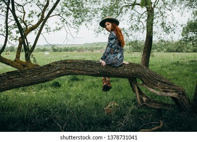 young girl in a straw hat travels green meadows.