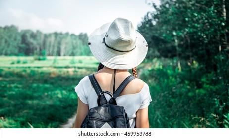 young girl in a straw hat travels green meadows