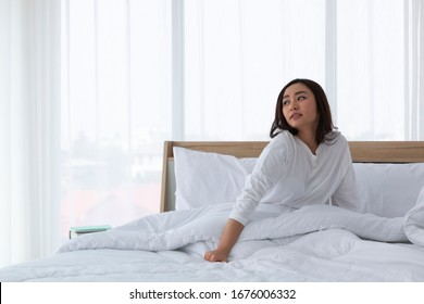 Young girl stretching in bed after wake up. Portrait of beautiful asian woman enjoying fresh soft bed linen mattress in bedroom. Woman Stretching in Her Bed. A Girl waking up in the Morning on bed.