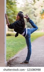 Young girl is stretching her leg, while holding on to a wall