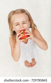 Young girl struggling to take a large bite of apple - looking up