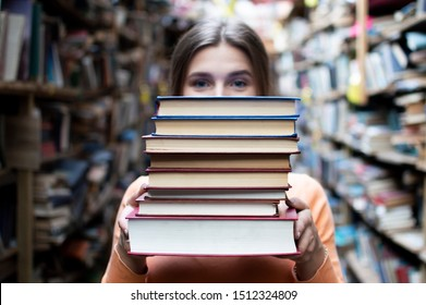 young girl student holds a stack of books in the library, she searches for literature and offers to read, a woman prepares for study, bookseller on the background of the bookstore, knowledge is power