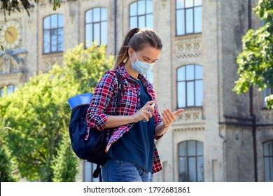 Young girl student in protective mask and school bag on her shoulder is standing outdoors near university and sanitize hands with antiseptic. Back to school after COVID-19 pandemic. New normal.