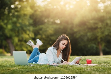 Young girl student in round glasses sitting on grass with laptop in front of university and studying homework. In the break between lessons he drinks coffee and listens to an electronic book, takes no