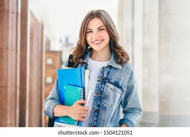 Young girl student smiling against university. Cute girl student holds folders and notebooks in hands. Learning, education concept