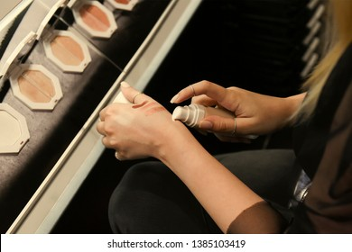 A young girl student testing, applying a foundation on her hands in a perfumery. A businesswoman is testing , trying, the tone, nuance of the powder by putting it on her arm. Selecting a make-up