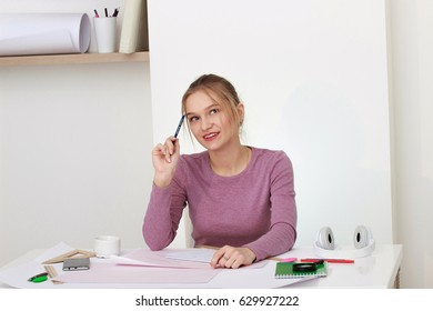 The young girl is studying while sitting at a white table