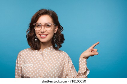 Young girl in stylish eyeglasses pointing away on blue background smiling at camera.