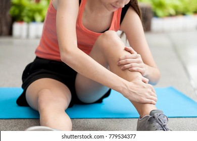 Young girl suffering or injury leg after do yoga.  russian woman or student has pain in his foot or shin while exercise or warm up. sport woman runner hurting holding painful sprained  ankle in pain
