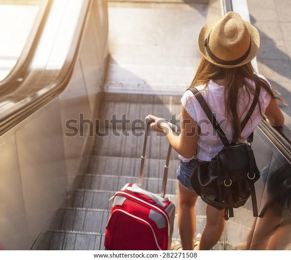 Uma jovem com uma mala na escada rolante.