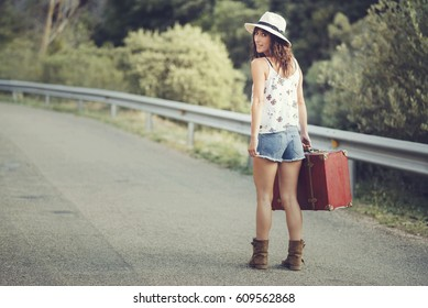 Young girl with a suitcase on the road