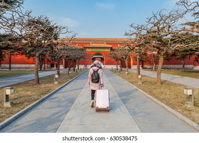 Young girl with suitcase on the way to explore the Forbidden City in Beijing, China. January 2017.