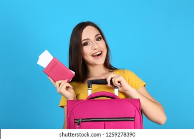 Young girl with suitcase and passport on blue background