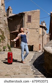 Young girl with a suitcase. Vacation concept. Old town in Tuscany, Italy