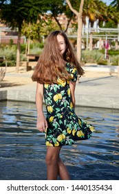 young girl with summer dress looking at camera with water in the background