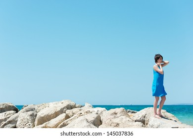 Young girl in a summer frock standing on rocks overlooking the ocean while enjoying the sunshine on a summer vacation, copyspace