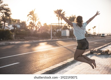 Young girl in summer jump near the road at sunset.