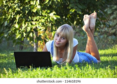 young girl in the summer park with a laptop