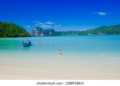 Young girl sunbathing on the clear and turquoise water of a tropical beach of Phi Phi island, Dalum bay, Phi Phi island, Krabi province, Thailand