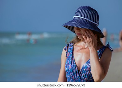Young girl in a sundress stands on the beach and hides her eyes behind the brim of her hat