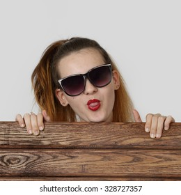 Young girl in sunglasses looks over wooden fence showing her tongue on gray background